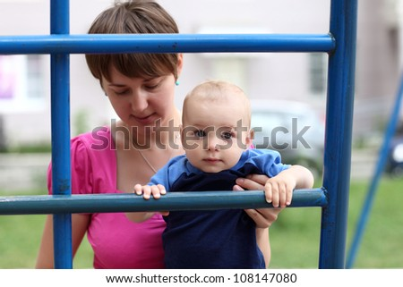 Portrait of baby with his mother on ladder at playground - stock photo