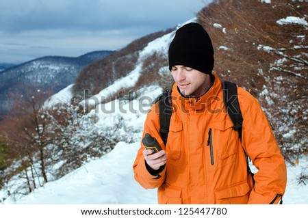 Portrait of backpacker holding GPS navigator, Global Positioning System device. Mountain winter landscape as a background. - stock photo