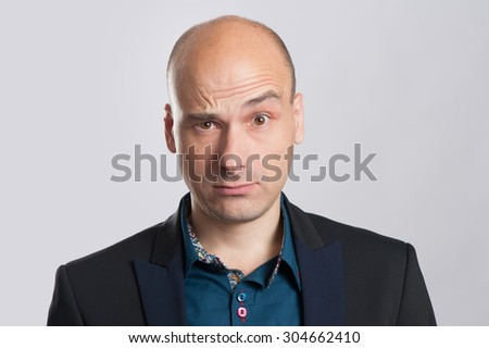 portrait of bald astonished businessman over gray background
