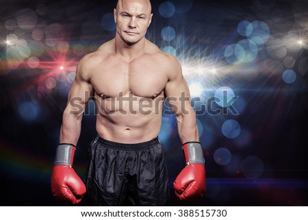 Portrait of bald man with boxing gloves against spotlights - stock photo
