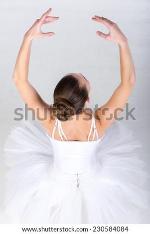 Portrait of ballerina in classical tutu in the grey studio. - stock photo