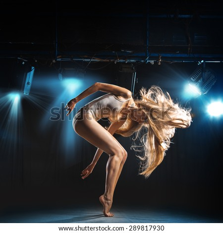 portrait of ballet dancer in pose on stage in theater - stock photo