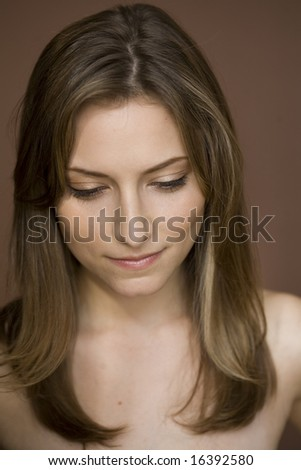 Portrait of bare-shouldered solitary woman, 20s, looking down in studio - stock photo