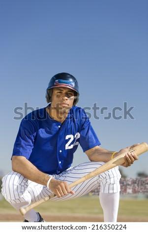 Portrait of baseball player holding bat - stock photo