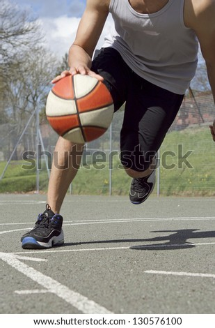 Portrait of Basketball Player dribbling the ball in Motion - stock photo
