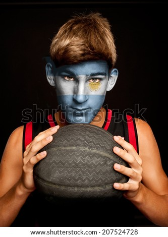 portrait of basketball player with argentinian flag painted on his face - stock photo