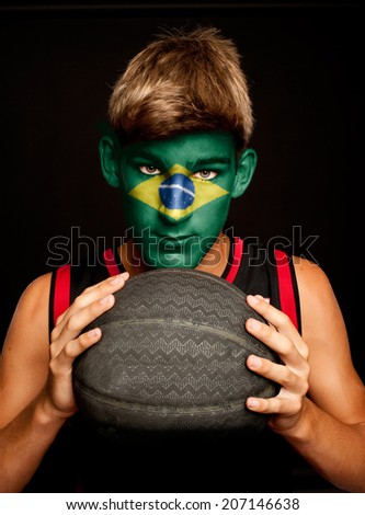 portrait of basketball player with brazilian flag painted on his face - stock photo