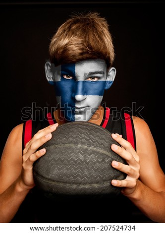 portrait of basketball player with finish flag painted on his face - stock photo