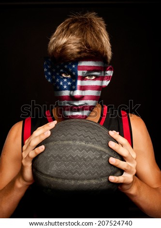 portrait of basketball player with united estates flag painted on his face - stock photo