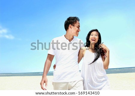 Portrait of beach couple in white dress having fun laughing together - stock photo