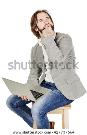 portrait of bearded business man working on his laptop and  and dreaming. emotions, facial expressions, feelings, body language, signs. image on  white studio background. - stock photo