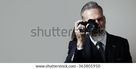 Portrait of bearded gentleman makes the photo on a classic camera. Wide