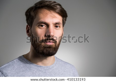 Portrait of bearded man in grey shirt looking at the camera on light grey background