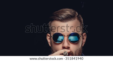 Portrait of bearded man in sunglasses. A man smoking cigare. Isolated on black background. - stock photo