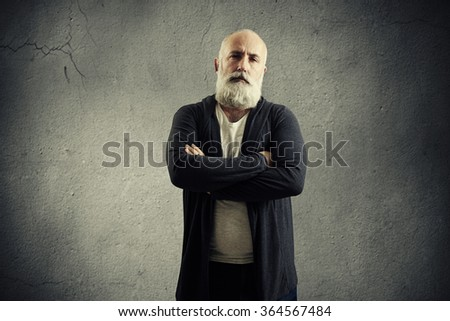 portrait of bearded senior man looking at camera over dark grey wall