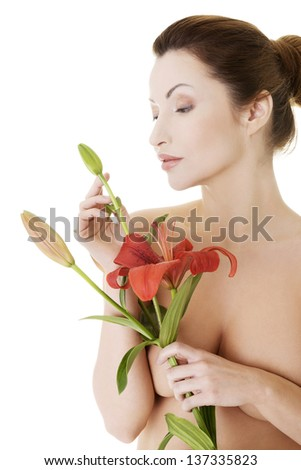 Portrait of beautiful adult woman with health skin and with red lily flower