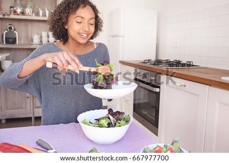 Portrait of beautiful african american adolescent girl serving salad, eating fruit and vegetables in home kitchen, smiling indoors. Young black woman cooking healthy vegan food, lifestyle in interior.