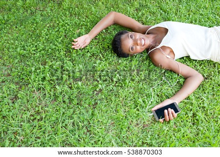 Portrait of beautiful african american woman laying on green grass in park using smart phone technology and headphones outdoors, relaxing smiling and looking. Black woman lifestyle, outdoors.