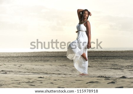 Portrait of beautiful African American woman meditating at the beach - stock photo