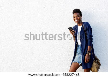 Portrait of beautiful african american woman standing against white wall and listening to music on mobile phone