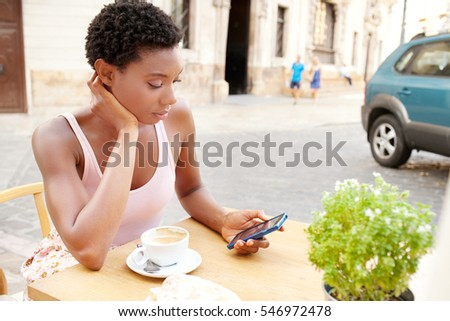Portrait of beautiful african american woman with shopping bags sitting at coffee shop terrace drinking, using smart phone in city, outdoors. Black girl technology travel recreation lifestyle.