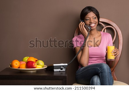 portrait of beautiful african girl using landline phone. woman talking on phone and drinking juice - stock photo