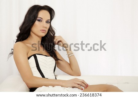 Portrait of beautiful and attractive young adult sensuality and sexy female brunette woman posing in white and black dress on the sofa