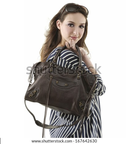 Portrait of beautiful and fashion model woman with blown hairs holding bag - stock photo