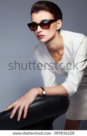 Portrait of beautiful and fashion woman in sunglasses, studio shot. Professional makeup and hairstyle