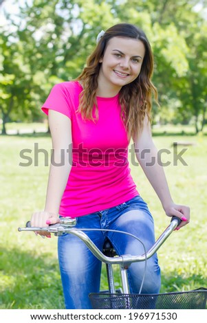 Portrait of beautiful and happy young woman enjoying nature riding a bike. - stock photo