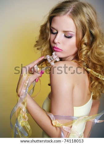 Portrait of beautiful and sexy woman with perfume bottle - stock photo