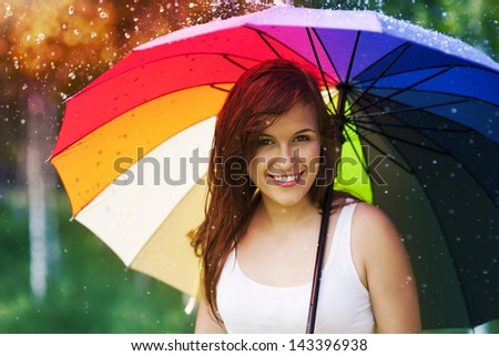 Portrait of beautiful and smiling woman with umbrella - stock photo