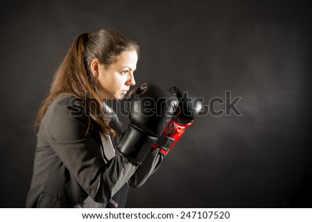 Portrait of beautiful and young business woman wearing boxing gloves. Young businesswoman in boxing concept. Ready to fight - stock photo