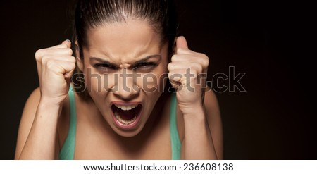 portrait of beautiful  angry woman on a dark background - stock photo