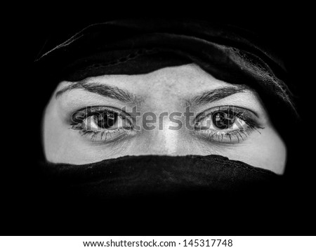 Portrait of beautiful Arab woman wearing black scarf in black and white
