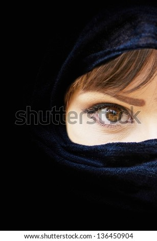 Portrait of beautiful Arab woman with brown eyes wearing black scarf - stock photo