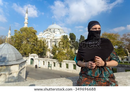 Portrait of beautiful Arabian Woman in traditional Muslim Clothing Middle East Urban landscape with Mosque and Minarets on Background - stock photo