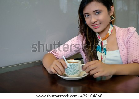 Portrait of beautiful asian college girl student sitting on campus cafe, feel relax and enjoy - stock photo