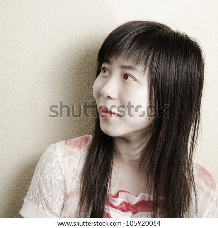 portrait of beautiful asian girl against yellow wall - stock photo