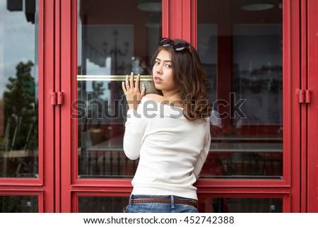 Portrait of beautiful asian girl standing with red door. - stock photo