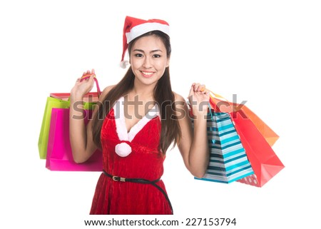 Portrait of beautiful Asian girl wearing Santa Claus clothes, holding colorful shopping bags.