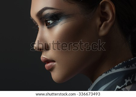 Portrait of beautiful asian girl with creative art make up. Picture taken in the studio on a black background.