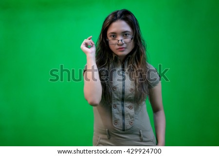 Portrait of beautiful asian girl with hand gestures on green screen for compositing