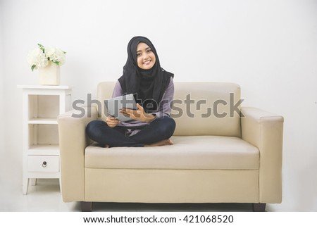 Portrait of beautiful asian girl with tablet computer at home