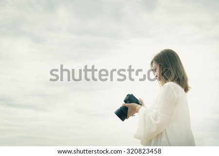Portrait of beautiful asian photographer on the sky background,vintage filter - stock photo