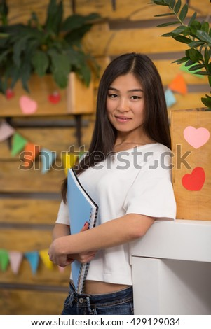 Portrait of beautiful Asian student standing with documents in library, college or university. Happy lady waiting for her classmates. - stock photo