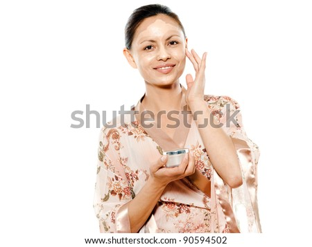Portrait of beautiful Asian woman applying facial mask in studio isolated on white background - stock photo