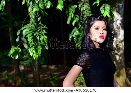 Portrait of beautiful Asian woman with red lipstick, pose at the forest