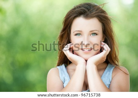 Portrait of beautiful attractive young smiling woman propping up her face with hands at summer green park