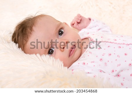 Portrait of Beautiful Baby Girl in Pink and White Top on Cream Fur Rug - stock photo